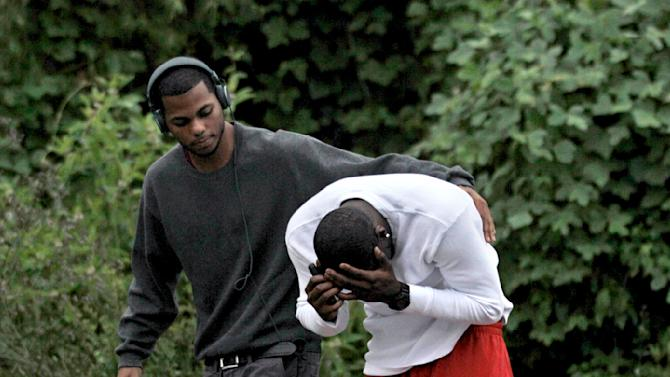 Mourners walk out of a housing complex at the scene of an overnight shooting, Sunday, June 10, 2012, in Auburn, Ala. Auburn Police Chief Tommy Dawson said authorities responded during the night to a report of multiple gunshot victims at the apartment complex, but he released no immediate information early Sunday. (AP Photo/David Goldman)