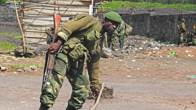A Congolese soldier at the last Congolese army check point in Munigi where fighting between the M23 and the Congolese army has been taking place in the past days near Goma, Congo, Monday, Nov. 19, 2012. Rebels believed to be backed by Rwanda fired mortars and machine guns Monday in a village on the outskirts of the provincial capital of Goma and threatened to attack the city which is protected by ragtag Congolese government troops backed by United Nations peacekeepers. The gunfire and explosions erupted in the early afternoon, hours after the M23 rebels said they were halting fighting in order to negotiate with the government of Congo. (AP Photo/Melanie Gouby)
