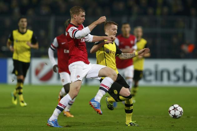 Borussia Dortmund's Reus challenges Arsenal's Mertesacker during Champions League soccer match in Dortmund