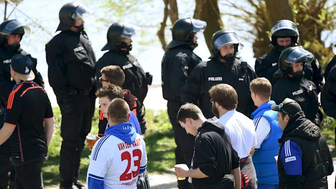 Police stand in front of the Weser stadium as fans of Hamburg SV make their way before the German Bundesliga first division soccer match between Werder Bremen and Hamburg SV in Bremen