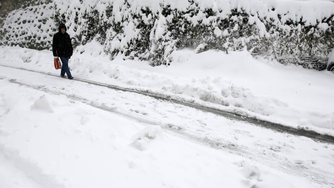 A man walks through the snow covered street in Belgrade, Serbia, Sunday, Dec. 9, 2012. Freezing temperatures and heavy snowfall have killed at least 5 people and caused travel chaos across the Balkans. (AP Photo/Darko Vojinovic)