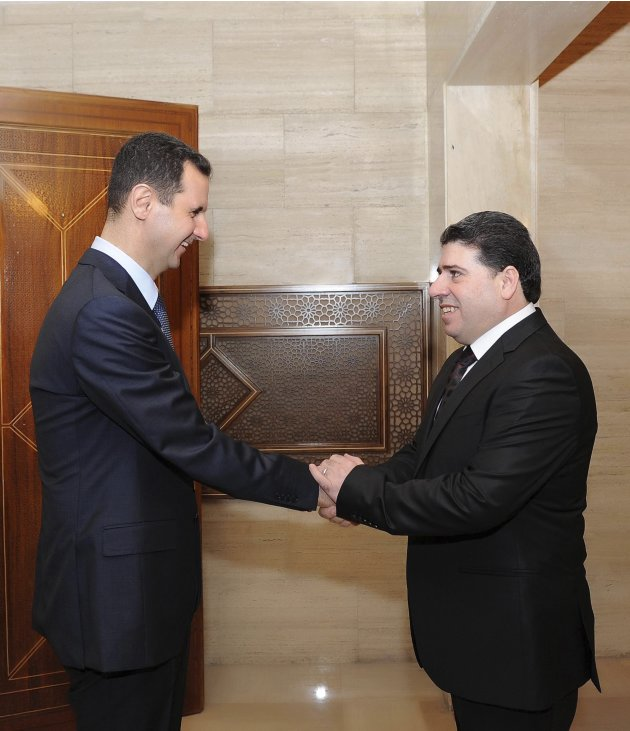 Syria's President Assad welcomes new Prime Minister Halki before a meeting in Damascus