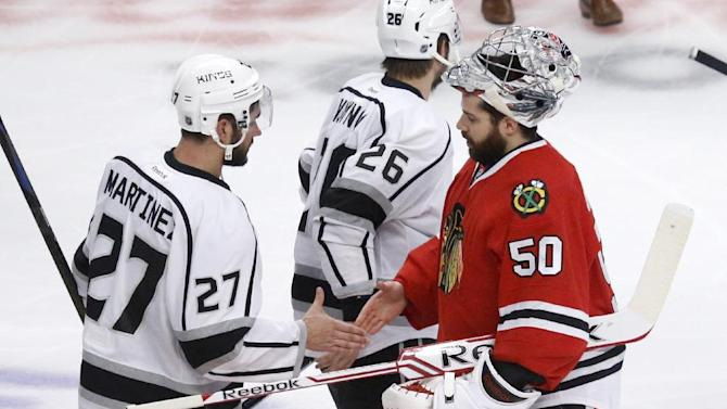 Los Angeles Kings defenseman Alec Martinez (27) shakes hands with Chicago Blackhawks goalie Corey Crawford (50) after the Kings defeated the Blackhawks 5-4 in the overtime period in Game 7 of the Western Conference finals in the NHL hockey Stanley Cup playoffs Sunday, June 1, 2014, in Chicago
