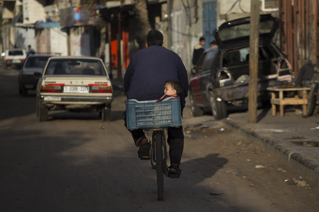 A Palestinian family rides a bike along a street of Gaza City, Sunday, Nov. 25, 2012. A leading Islamic cleric in the Gaza Strip has ruled it a sin to violate the recent cease-fire between Israel and the Hamas militant group that governs the Palestinian territory according a religious legitimacy to the truce and giving the Gaza government strong backing to enforce it. (AP Photo/Bernat Armangue)