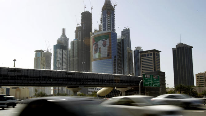 FILE - This March 9, 2011, file photo, shows a large image of Sheik Mohammed bin Rashid Al-Maktoum, UAE Prime Minister and ruler of Dubai, rear left, and Sheik Khalifa bin Zayed Al-Nahyan, UAE President, right, on a tower at Internet City, as cars pass drive on Sheikh Zayed's highway in Dubai, United Arab Emirates. An upcoming U.N. gathering that will seek agreements on Internet oversight is raising alarms from a broad coalition of critics including the U.S. government, tech giants such as Google and rights groups concerned that changes could lead to greater efforts to filter the Web and stifle innovation for cyberspace. (AP Photo/Kamran Jebreili, File)