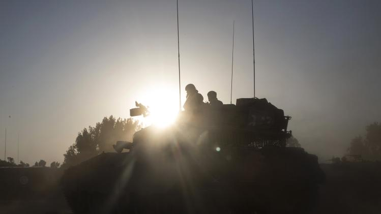 Israeli soldiers ride a tank outside the central Gaza Strip