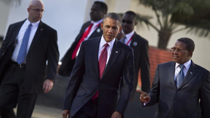 U.S. President Barack Obama walks with Tanzanian President Jakaya Kikwete, right, to a joint press conference after meeting together at State House in Dar es Salaam, Tanzania Monday, July 1, 2013. Teeming crowds and blaring horns welcomed President Barack Obama to Tanzania's largest city, where the U.S. president's likeness is everywhere as he arrived on the last leg of his three-country tour of the African continent. (AP Photo/Ben Curtis)