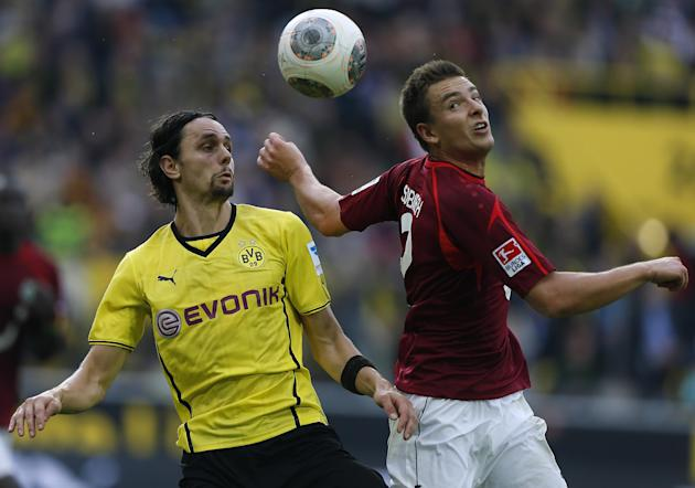 Dortmund's Neven Subotic of Serbia, left, and Hannover's Leon Andreasen of Denmark challenge for the ball during the German first division Bundesliga soccer match between BvB Borussia Dortmund and Han