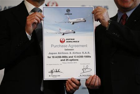 Japan Airlines President Ueki holds an agreement document with Airbus Chief Executive Bregier as they pose during their joint news conference in Tokyo