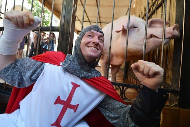 "An English Fan Dressed As A Knight Poses Infront Of The Cage Of Funtik The ""psychic"" Pig In The Euro 2012 Fanzone In AFP/Getty Images"