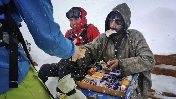 In this photo taken Friday, Feb. 22, 2013, A Kashmiri vendor sells chocolate as he sits beside a foreign tourist in Gulmarg, Kashmir. Gulmarg, a ski resort nestled in the Himalayan mountains in Indian-held Kashmir is one of the most militarized places on earth. (AP Photo/Kevin Frayer)