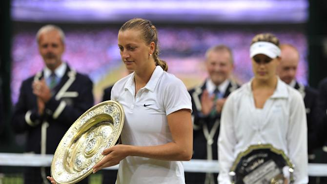 Czech Republic's Petra Kvitova (L) holds the winner's Venus Rosewater Dish and Canada's Eugenie Bouchard (R) holds the runners-up trophy after the women's singles final match on day 12 of the 2014 Wimbledon Championships on July 5, 2014