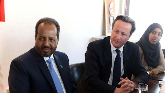 Britain's Prime Minister David Cameron and the President of Somalia Hassan Sheikh Mohamud, left, listen during a meeting in London, Tuesday May 7, 2013, with members of the Somali diaspora living in Britain, ahead of the Somalia Conference later in the day. British Prime Minister David Cameron is welcoming Somalia's president and a host of international leaders to London for a conference aimed at securing support for the government in Mogadishu after two decades of conflict. (AP Photo/Steve Parsons, Pool)