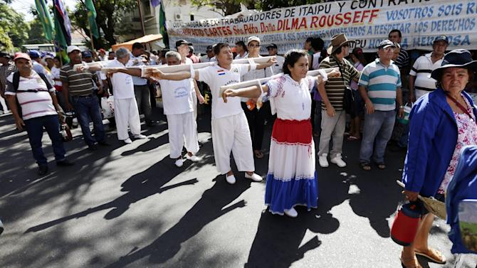Former workers of Itaipu dam contractor companies Unicom and Conempa, from left in white, Pablo Garcete, Roque Samudio Roberto Gonzalez, and Rosa Caceres, the wife of a former worker of Unicom, march in the streets of Asuncion towards the Ministry of labor, in a symbolic crucifixion, in Paraguay, Monday, Jan. 26, 2015. The demontrators are part of a group that for the last 25 years, after the construction on the dam was completed, is demanding compensation benefits from the contractors. The Itaipu hydroelectric dam on the Parana River straddles the Brazil-Paraguay border. (AP Photo/Jorge Saenz)