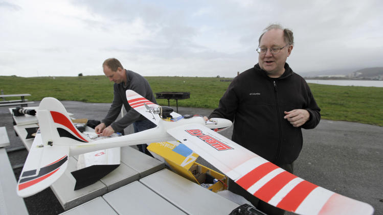 In this March, 28, 2012, photo, Mark Harrison, right, and Andreas Oesterer, left, prepare their drones for a flight over a waterfront park in Berkeley, Calif. Interest in the domestic use of drones is surging among public agencies and private citizens alike, including a thriving subculture of amateur hobbyists, even as the prospect of countless tiny but powerful eyes circling in the skies raises serious privacy concerns. (AP Photo/Eric Risberg)