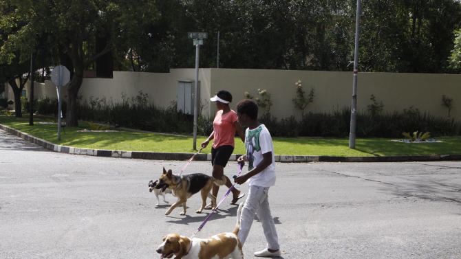 "People walk their dogs outside the home of former president Nelson Mandela in Johannesburg, Thursday, Dec. 27 2012. President Jacob Zuma made critical remarks about pet care that touch on sensitive race relations in South Africa, which was dominated by whites until apartheid was dismantled almost two decades ago, The Star newspaper reported Thursday. The newspaper cited Zuma as saying in a speech Wednesday that the idea of having a pet is part of ""white culture"" and that people should focus on family welfare. (AP Photo/Denis Farrell)"