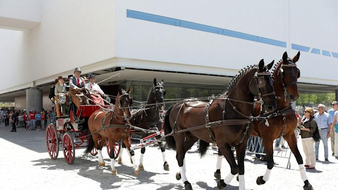 Horses pull a carriage outside the new building of the National Coach Museum in Lisbon on its 110th anniversary Saturday, May 23, 2015. Thousands queued to visit the museum which reopened to the public Saturday in a sleek, minimalist 21st-century building. (AP Photo/Armando Franca)