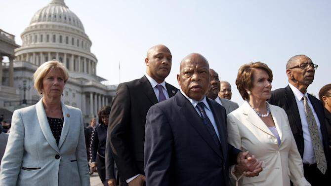 Rep. John Lewis, D-Ga., center, holds hands with House Minority Leader Nancy Pelosi of Calif., next to Rep. Bobby Rush, D-Ill., right, as House Democrats leave the Capitol in protest of a House vote to hold Attorney General Eric Holder in contempt of Congress, Thursday, June 28, 2012, on Capitol Hill in Washington. (AP Photo/Jacquelyn Martin)