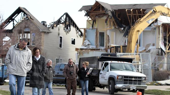 Brett, left, and his wife Nikki Cocherell walk away from the site where their home was being demolished in Indianapolis, Tuesday, Nov. 27, 2012.  City building inspectors last week ordered the demolition of 29 houses by Dec. 20. Four other homes, including two that were leveled in the Nov. 10 explosion, are being maintained as police investigate what they believe was an intentional natural gas explosion.  (AP Photo/Michael Conroy)
