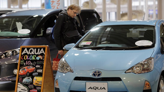 "A man inspects an ""Aqua"" at a Toyota Motor Corp. showroom in Tokyo Monday, Nov. 5, 2012. Toyota's quarterly profit tripled, driven by a recovery from natural disasters, and the company raised its full-year earnings forecast despite a sales slump in China. (AP Photo/Koji Sasahara)"