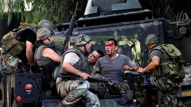 Lebanese army soldiers help injured soldiers after clashes between followers of a radical Sunni cleric Sheik Ahmad al-Assir and Shiite gunmen, in the southern port city of Sidon, Lebanon, Monday, June 24, 2013. Lebanese troops battled heavily armed followers of a hard-line Sunni cleric holed up in a mosque complex in a southern port city on Monday, the second day of fighting that has left more than a dozen of soldiers dead, the military said. (AP Photo/Mohammed Zaatari)