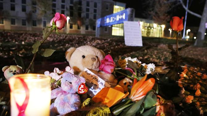 Candles and teddy bears are placed at Danvers High School prior to a candlelight vigil to mourn the death of Colleen Ritzer, a 24-year-old math teacher at Danvers High School on Wednesday, Oct 23, 2013, in Danvers, Mass. Ritzer was found slain in woods behind the high school, and Danvers High School student Philip Chism, 14, who was found walking along a state highway overnight was charged with killing her. (AP Photo/ Bizuayehu Tesfaye)