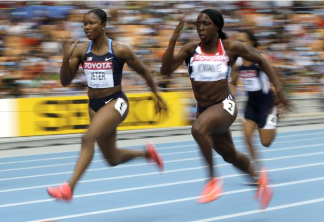 USA's Carmelita Jeter, left, and Britain's Jeanette Kwakye compete in a heat of the women's 100-meter race at the World Athletics Championships in Daegu, South Korea, Sunday, Aug. 28, 2011. (AP Photo/