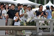 People gather to pray at the memorial for victims of the Hiroshima bombings at the Peace Memorial Park in Hiroshima, Japan