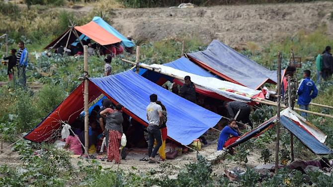 Nepalese people stay outside in tents on the outskirts of Kathmandu on April 26, 2015 after an earthquake hit the nation