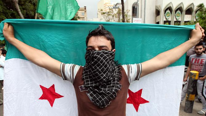Supporter of an Islamic group, holds up a Syrian revolution flag, as he march during a demonstration against the Syrian regime, after Friday prayers, in Beirut, Lebanon, Friday, April 20, 2012.  The United Nations hopes to have 30 cease-fire monitors in Syria next week and plans are already being made for the deployment of up to 300, a spokesman for international envoy Kofi Annan said Friday. (AP Photo/Bilal Hussein)