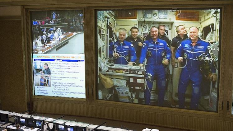 In this image provided by NASA shows a view from the balcony of the Russian Mission Control Center shows live television of the Expedition 39 crew members gathered together on the International Space Station a few hours after the Soyuz TMA-12M spacecraft docked on Friday, March 28, 2014, in Korolev, Russia. Pictured are Expedition 39 crew members Flight Engineer Steve Swanson of NASA, left, Commander Koichi Wakata of the Japan Aerospace Exploration Agency, JAXA, back left, Flight Engineer Alexander Skvortsov of the Russian Federal Space Agency, Roscosmos, front center, Flight Engineer Rick Mastracchio of NASA, back center, Flight Engineer Mikhail Tyurin of Roscosmos, back right and Flight Engineer Oleg Artemyev of Roscosmos, front right. Swanson, Skvortsov, and Oleg's arrival to the International Space Station comes two days after they launched from the Baikonur Cosmodrome in Kazakhstan. Photo Credit (NASA/Joel Kowsky)