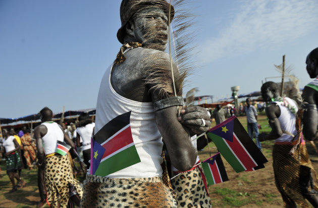 A man holds South Sudanese flags as he prepares to dance at the country's anniversary celebrations, at the John Garang mausoleum in Juba, South Sudan, Monday, July 9, 2012. The world's newest nation,