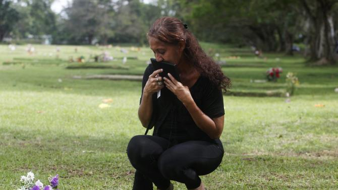 Carmen Campos kisses a photograph next to a grave at the Jardin de Paz cemetery, in remembrance of the 25th anniversary of the U.S invasion of Panama, in Panama City