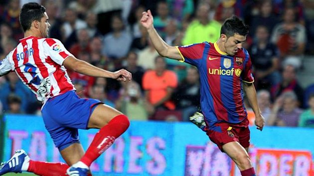 Barcelon's striker David Villa (R) shoots in presence of Sporting de Gijon's Alberto Tomas Botia (L), during their Spanish Primera Division soccer match played at the Camp Nou stadium in Barcelona, Spain