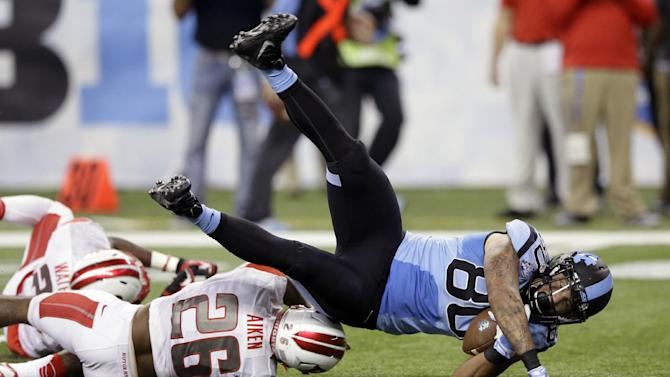 North Carolina tight end Jack Tabb (80) is upended by Rutgers defensive back Johnathan Aiken (26) during the first half of the Quick Lane Bowl NCAA college football game, Friday, Dec. 26, 2014, in Detroit. (AP Photo/Carlos Osorio)