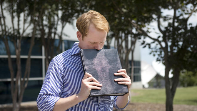 WDBJ news anchor Chris Hurst pauses as he is overcome with emotion while holding a photo album that was created by fellow reporter and girlfriend Alison Parker, in Roanoke, Va., Wednesday, Aug. 26, 2015. Vester Lee Flanagan opened fire during a live on-air interview for WDBJ, killing Parker and cameraman Adam Ward. (Erica Yoon/The Roanoke Times via AP) LOCAL STATIONS OUT; LOCAL INTERNET OUT; LOCAL PRINT OUT (SALEM TIMES REGISTER; FINCASTLE HERALD; CHRISTIANSBURG NEWS MESSENGER; RADFORD NEWS JOURNAL; ROANOKE STAR SENTINEL; MANDATORY CREDIT MAGS OUT/ NO SALES