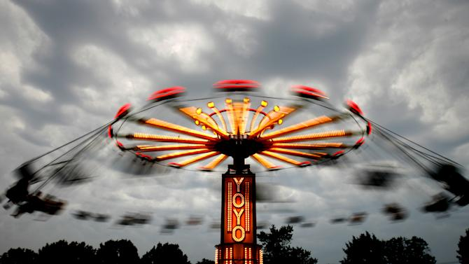 A passing storm brought a halt to rides Friday, June 29, 2012 at the 26th annual Italian-American Festival being held this weekend at the Stark County Fairgrounds in Canton, Ohio. A wave of violent storms sweeping through the mid-Atlantic following a day of record-setting heat in Washington, D.C., has knocked out power to nearly 2 million people. The storms converged Friday night on Washington, D.C., Maryland, Virginia and West Virginia. West Virginia Gov. Earl Ray Tomblin declared a state of emergency after more than 500,000 customers in 27 counties were left without electricity.  (AP Photo/The Repository, Bob Rossiter)