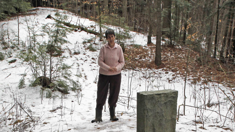 In this Thursday, March 28, 2013 photo, Rep. Anne Donahue looks at a memorial stone at the site of a Vermont State Hospital cemetery in Waterbury, Vt.  Vermont mental health advocates are trying to decide what to do with the abandoned cemetery near the former State Hospital, which was forced to move by flooding from Tropical Storm Irene. (AP Photo/Toby Talbot)