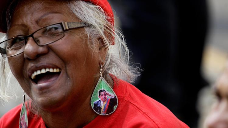A supporter of Venezuela's President Hugo Chavez wears earrings decorated with Chavez's image at a rally in Caracas, Venezuela, Wednesday, Jan. 23, 2013. The cult of personality that Chavez long nurtured has been flourishing like never before as he confronts an increasingly difficult struggle against the mysterious cancer that afflicts him. (AP Photo/Fernando Llano)