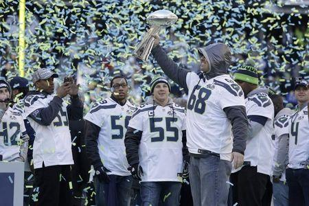 Seahawks' Giacomini holds the Vince Lombardi Trophy at Century Link Field after the NFL team's Super Bowl victory parade in Seattle