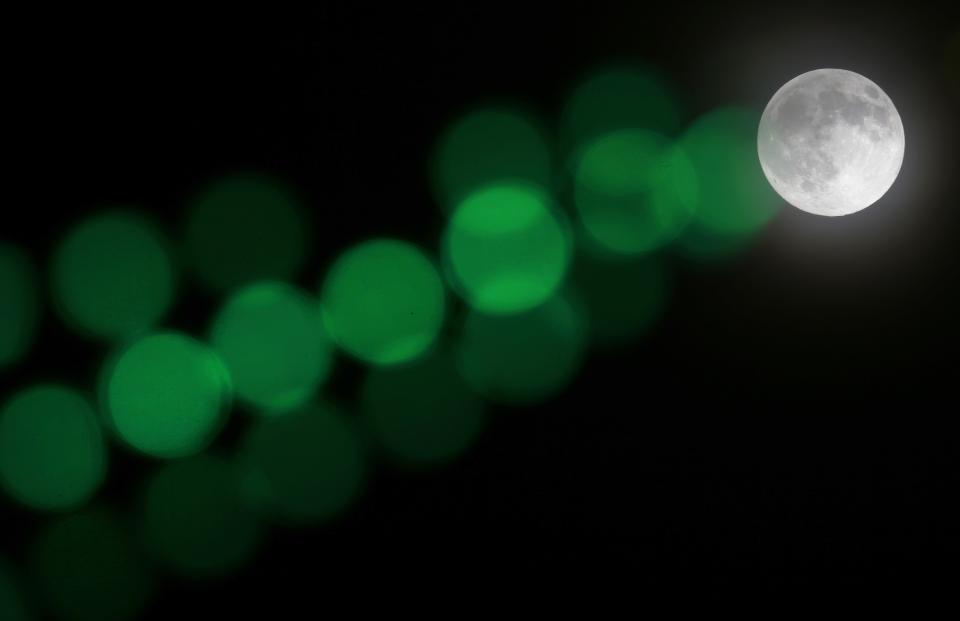 A full moon rises through a hazy sky past a string of green lights, Saturday, June 22, 2013, in Baltimore. The moon, which will reach its full stage on Sunday, is expected to be 13.5 percent closer to earth during a phenomenon known as supermoon. (AP Photo/Patrick Semansky)
