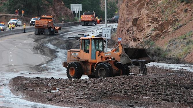 A bulldozer works to clear mud from Hwy. 24 after a mudslide closed the road just west of Manitou Springs, Colo., Wednesday, July 10, 2013. A thunderstorm has sent rocks, mud, debris and running water rushing down part of U.S. 24 in a canyon in Manitou Springs, leaving some vehicles covered or stuck in mud. (AP Photo/The Gazette, Jerilee Bennett) MAGS OUT