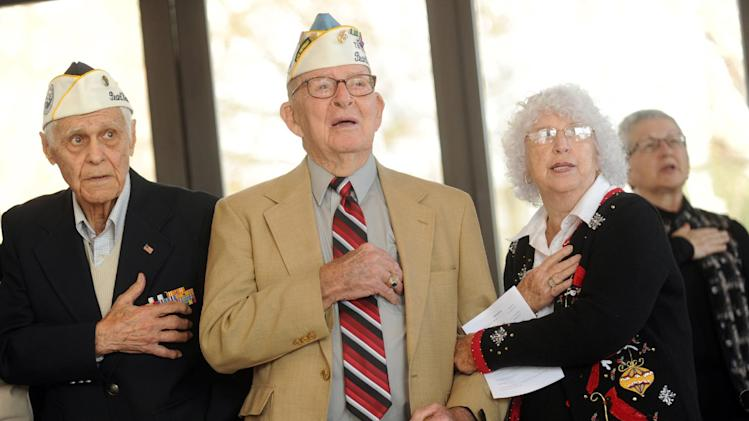 Pearl Harbor survivors Ray Perlingiero, left, and Bill Ferguson, with his wife Ailene, recite the Pledge of Allegiance during a Pearl Harbor memorial service Friday, Dec. 7, 2012, in Knoxville, Tenn. During the Japanese attack, Ferguson was aboard the light cruiser USS Detroit and Perlingiero was an Army Air Forces corporal based at Hickam Field. (AP Photo/Paul Efird, Knoxville News Sentinel)