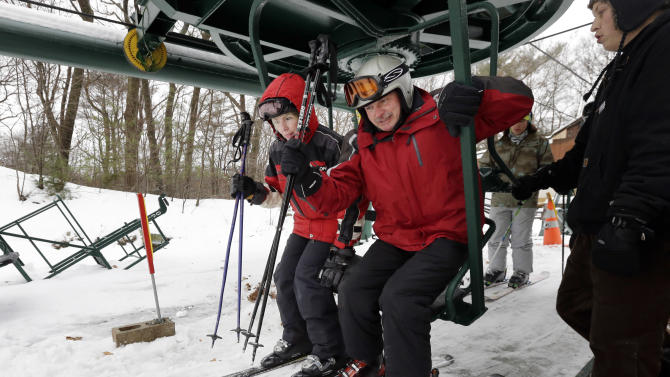 Skiers get on a chairlift at Blue Hills Ski Area Sunday, Dec. 15, 2013 in Canton, Mass. The National Weather Service says parts of Massachusetts, Connecticut and Rhode Island will see snow accumulation of between 6 inches and a foot. (AP Photo/Steven Senne)