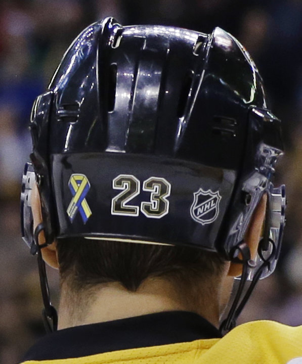 "FILE - In this April 17, 2013, file photo, Boston Bruins center Chris Kelly wears a ""Boston Strong"" decal, left, on his helmet during an NHL hockey game against the Buffalo Sabres in Boston. With thei"