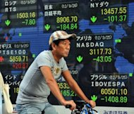 A cyclist passes a share prices board in the window of a securities company in Tokyo. A string of upbeat data from the United States and a rally on Wall Street boosted Asian markets on Friday, while growing confidence in the global outlook kept the safe-haven yen under pressure
