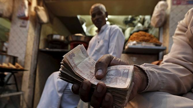 File photo shows a street side restaurant owner holding a bundle of Indian currency notes as he sits outside his restaurant in New Delhi