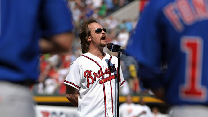 FILE - In this April 5, 2010, file photo, county music singer Travis Tritt sings the national anthem before a baseball game between the Atlanta Braves and the Chicago Cubs in Atlanta.  Tritt will perform the national anthem prior to the NCAA Final Four college basketball championship game between Michigan and Louisville on Monday night, April 8, 2013. (AP Photo/Rich Addicks, File)