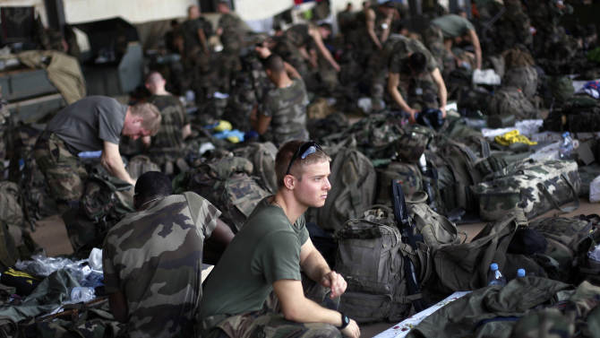 French troops gather in a hangar at Bamako's airport Tuesday Jan. 15 2013.  French forces led an all-night aerial bombing campaign Tuesday to wrest control of a small Malian town from armed Islamist extremists who seized the area, including its strategic military camp. A a convoy of 40 to 50 trucks carrying French troops crossed into Mali from Ivory Coast as France prepares for a possible land assault. Several thousand soldiers from the nations neighboring Mali are also expected to begin arriving in coming days. (AP Photo/Jerome Delay)