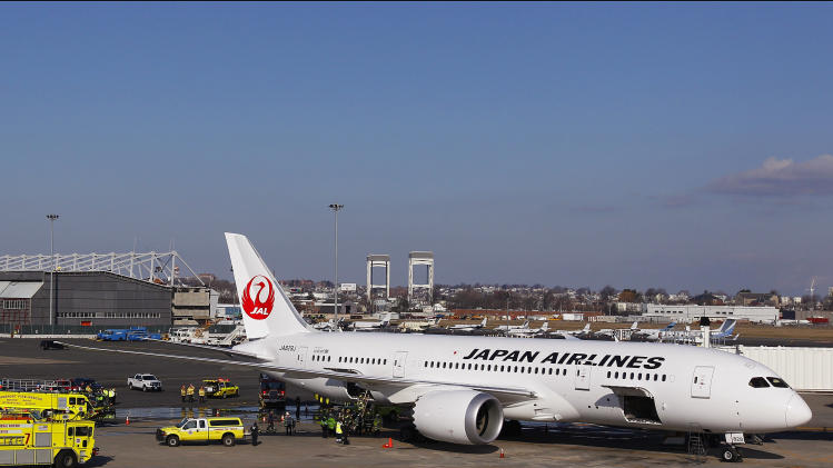 A Japan Airlines Boeing 787 Dreamliner jet aircraft is surrounded by emergency vehicles while parked at a terminal E gate at Logan International Airport in Boston, Monday, Jan. 7, 2013. A small electrical fire filled the cabin of the JAL aircraft with smoke Monday morning about 15 minutes after it landed in Boston. (AP Photo/Stephan Savoia)